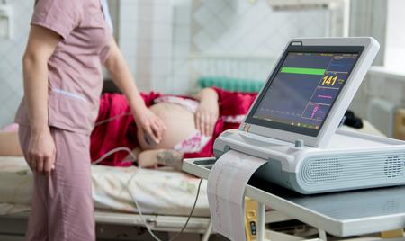 La mujer embarazada con el electrocardiógrafo chequea a su bebé. Monitoreo cardíaco fetal. Diagnóstico, asistencia sanitaria, servicio médico.