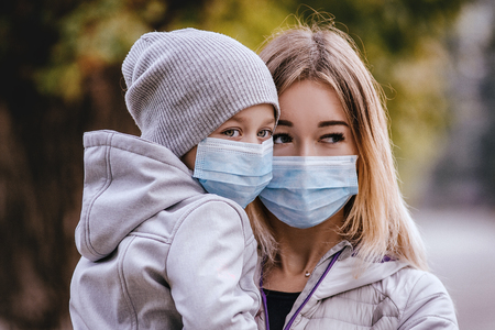 a girl with a child stands on the road in a protective medical mask. Dense smog on the streets. Epidemic of the flu Stockfoto