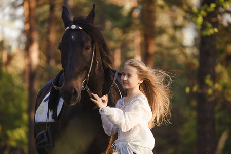Young blonde girl stroking a brown horse. Stockfoto