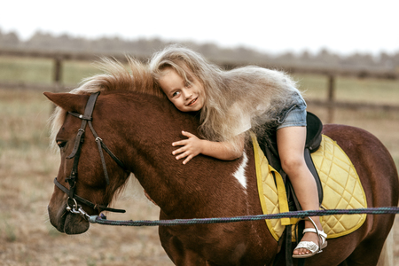 Adorable little girl riding a pony at summer Stockfoto