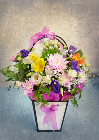 Beautiful tender bouquet of flowers in white box on wooden background with space for text