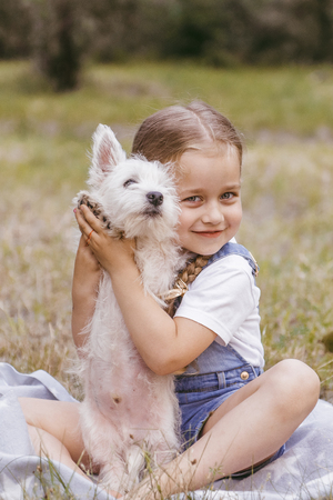 Adorable little girl holding a Westie puppy