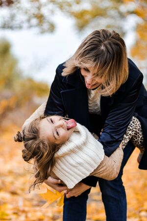 motmother and daughter in autumn park have funher and daughter in autumn park have fun
