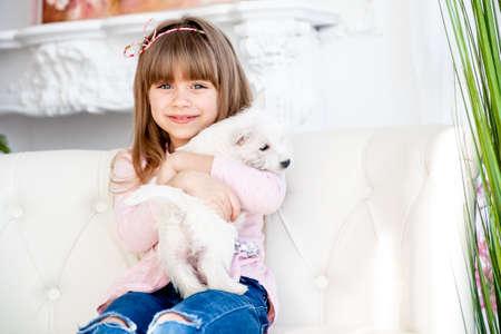 child hugs a white terrier puppy Zdjęcie Seryjne