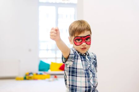 Toddler super hero in a red painted mask at home