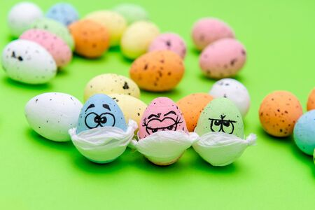 Funny three eggs in a mask for Easter on a green background
