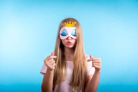 Beautiful woman in pajamas and sleeping mask on a light blue background. for the coming dream Standard-Bild