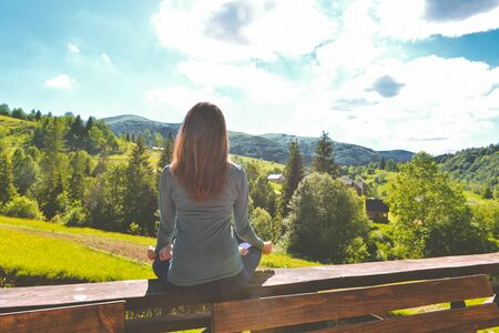 young fitness woman practice yoga with a view of the mountains
