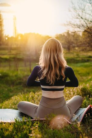 Slender girl doing yoga in the park at sunset. Outdoor healthcare. View from the back