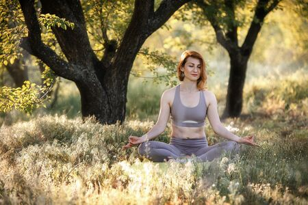 A girl is meditating under a tree. Yoga classes in nature