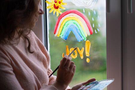 woman writes the word joy on the window