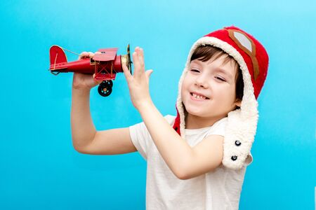 An impressive boy in a pilots cap raised his hands up holding a retro toy airplane, isolated on a blue background. Imagination of a pilot, aviation concept