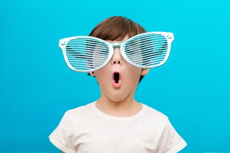Cheerful little boy in big glasses express a surprised face isolated on blue background Standard-Bild