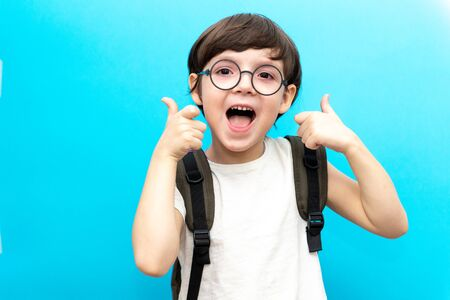 For the first time to school. Happy smiling boy with thumb up. A child from elementary school in uniform. Toddler indoors on a blue background. Funny baby
