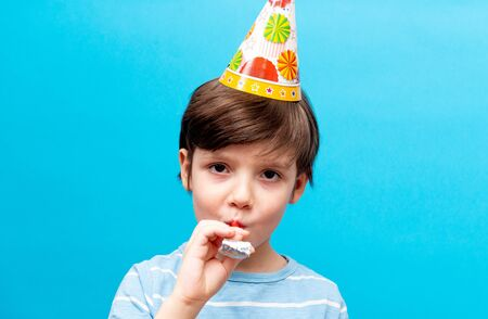 Happy Caucasian boy celebrates his birthday blowing a whistle on a blue background. Holiday and party concept with space for text.