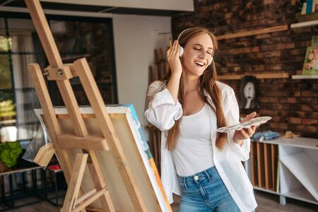 Beautiful girl singing and painting. Young beautiful woman painting artist while working in studio, listening to music in headphones