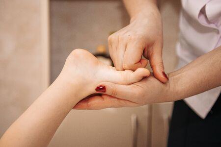 A woman does massage for a little girl. Wellness foot massage, with flat feet