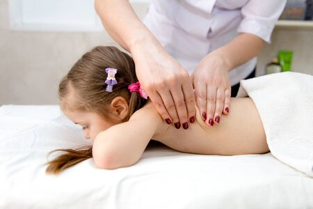 woman doing massage to a little girl. Wellness massage for scoliosis