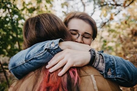 Charming young women kissing gently loving each other stroking touching face skin enjoying romantic tender moments on picnic date in the countryside.