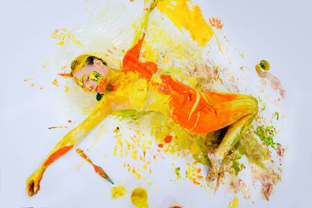 Woman painted with colorful paint lying on white background, body art, feeling free