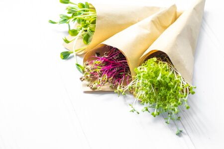 Sprouts of radish sunflower and beet in paper package lying on white background