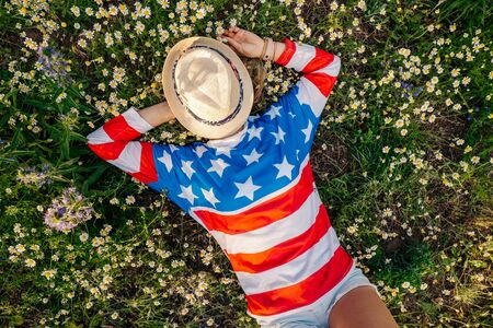 Cheerful woman patriot lying in daisy field wearing american flag T-shirt, independence day