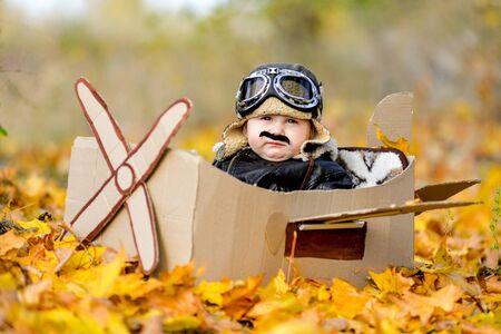 Very cute boy sitting in cardboard plane, future pilot, lifetime dream profession