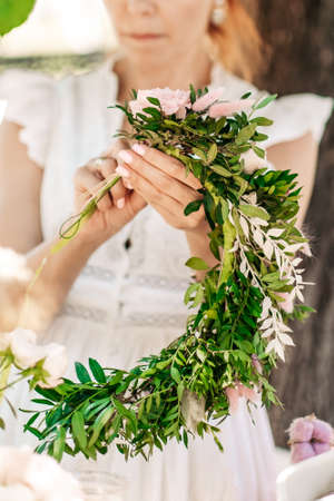 Workshop florist, making bouquets and flower arrangements. Girl makes wreath at head. Process of weaving a wreath with herbs and flowers. Lesson of florists close-up. Copy space