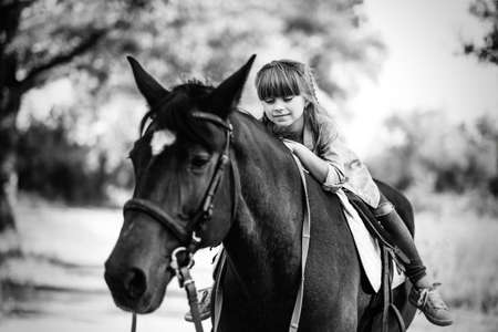Cute little girl with long hair riding a horse outdoors. Pet therapy