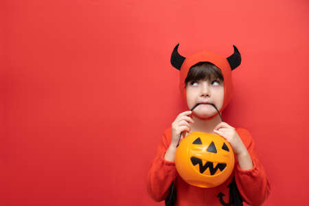 Celebrating Halloween. A boy with a basket of pumpkins in his mouth is dressed in a halloween party devil costume. Studio portrait isolated on red background