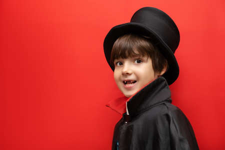 halloween, holiday and childhood concept - boy in dracula costume with black cape and top hat on his head on red background