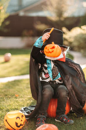 Happy Halloween. A child in a medical mask in a dracula costume sits on a pumpkin in his yard. Reklamní fotografie