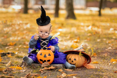 Happy Halloween Cute little witch with pumpkins. Beautiful young child girl in suit outdoors.