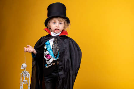 halloween, holiday and childhood concept - boy in dracula costume with black cape and top hat on his head on yellow background