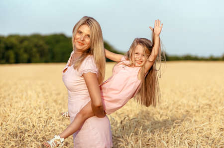 Cheerful daughter and mother having fun in wheat field, happy time together