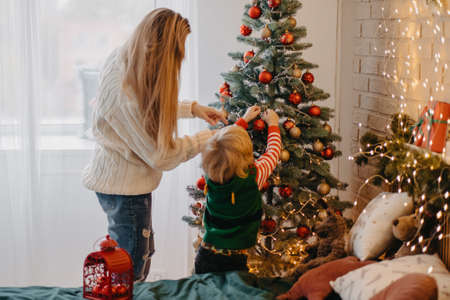 happy mother and cute little son decorating christmas tree together