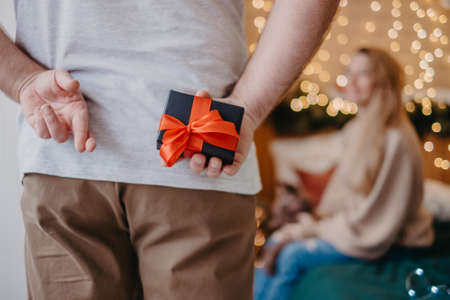 Man crossed fingers hoping for good luck and holding gift box, preparing to make proposal for girlfriend, Christmas magic atmosphere