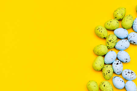 Colorful easter eggs on yellow paper background