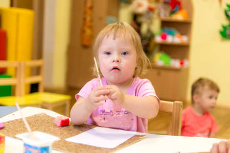 UKRAINE , KREMENCHUK - August 7, 2019: Girl with Down Syndrome draws on paper a rehabilitation center for special children
