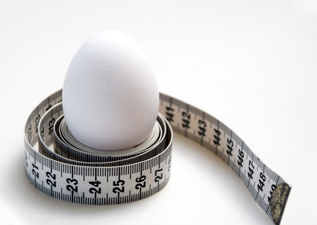 Egg wrapped around with a measuring tape Stock Photo