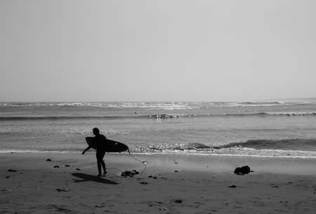 Black and white picture of female surfer walking along the beach in the north of Peru
