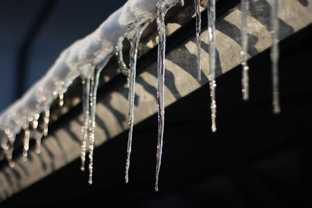 Icicles hanging in the sun on a carport