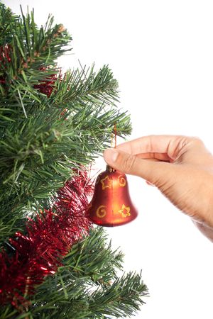 hand hanging bell on christmas treeisolated on white photo