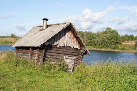 badhuis: oude scheve bad huis in de buurt van de rivier  Stockfoto