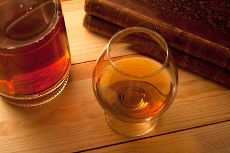 glass with cognac bottle and books photo