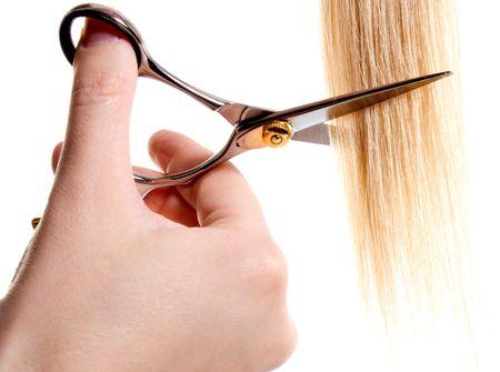 scissors cutting lock of hair isolated on white Standard-Bild