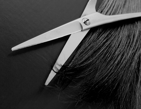 haircutting: Scissors and lock of hair. selective focus Stock Photo