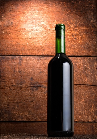 bottle of red wine on wooden background photo