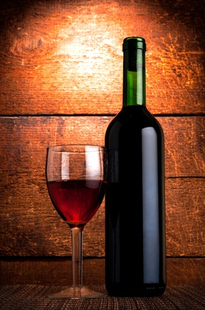 bottle of red wine  and glass on wooden background photo