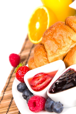 croissant with juice, jam and berries